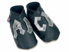 AB CD logo in the style of AC DC in metal on black soft leather baby shoes.